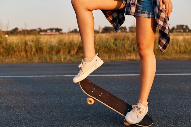 Persona femminile sconosciuta con gambe lunghe e belle che indossano scarpe da ginnastica bianche in sella a skateboard, pattinatore senza volto che fa skateboard in estate, colpo all'aperto.