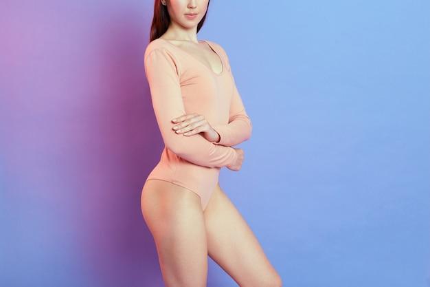 Неизвестная женщина с идеальной фигурой позирует со сложенными руками на теле, женщина с идеальным телом, девушка с темными волосами в бежевом боди, изолированная над синей стеной с розовым неоновым светом.