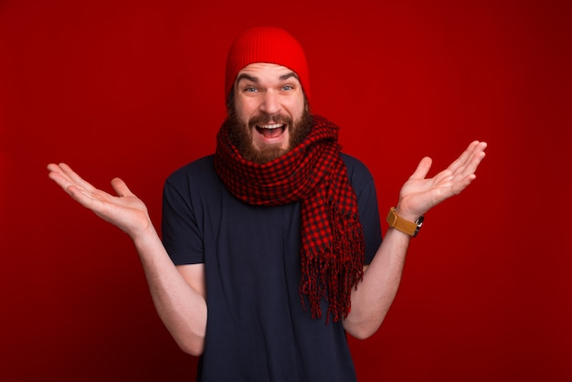 Unknown gesture of bearded guy, in red scarf and hat, standing over red space