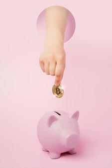 암호 화폐를 저장하는 배경에 황금 비트코인과 분홍색 돼지 저금통이 있는 알 수 없는 손