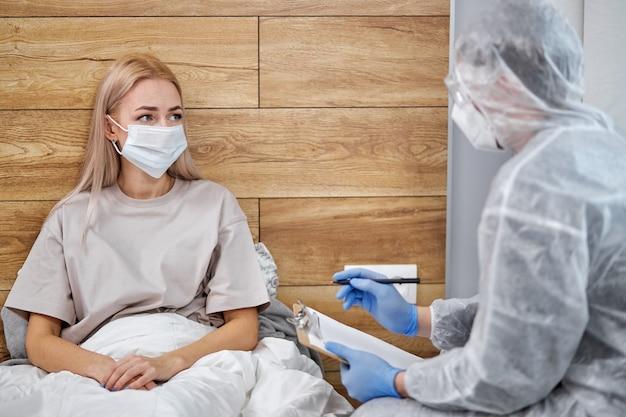 不明な男性-スーツを着た医師と病気の患者が自宅に座って現在の健康診断について話し合っています。コロナウイルスcovid-19パンデミックおよび自己隔離検疫中は外出禁止令。