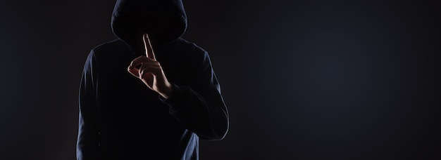 Unknown man in the hood holding index finger on lips asking for silence. secret concept, panoramic mock-up with space for text