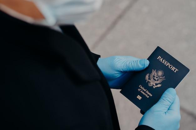Unknown man tourist wears rubber medical gloves, holds passport