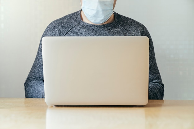 Unknown man typing on the laptop while is wearing a mask