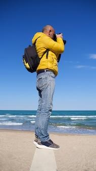 Неизвестный мужчина со своим фотооборудованием фотографирует на пляже в солнечный день с голубым небом