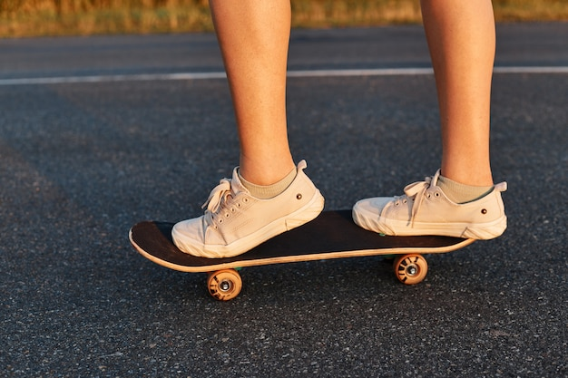 Persona sconosciuta che fa skateboard su strada asfaltata, gambe di donna su longboard, donna senza volto che indossa scarpe da ginnastica bianche sullo skateboard.