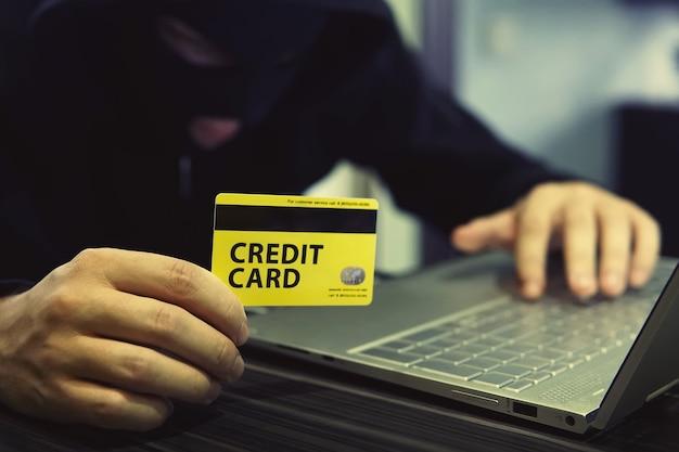 Неизвестный человек использует компьютер и кредитную карту для совершения киберпреступлений. злоумышленник использует интернет для кражи денег. получение денег с банковского счета путем мошенничества с платежными картами. взлом онлайн-банкинга.