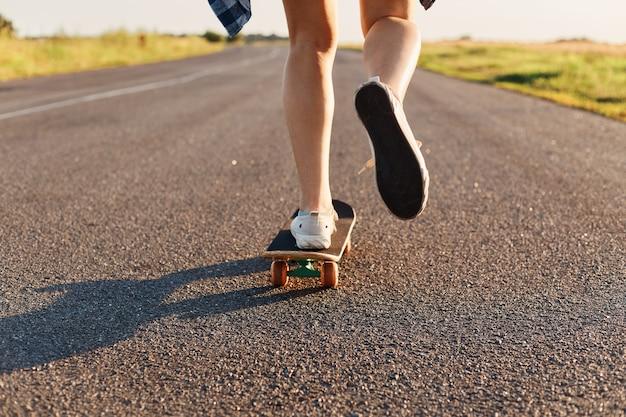 アスファルト道路でスケートボードに乗って白いスニーカーを履いている未知の人、通りでスケートボードをしている若い女性の足。