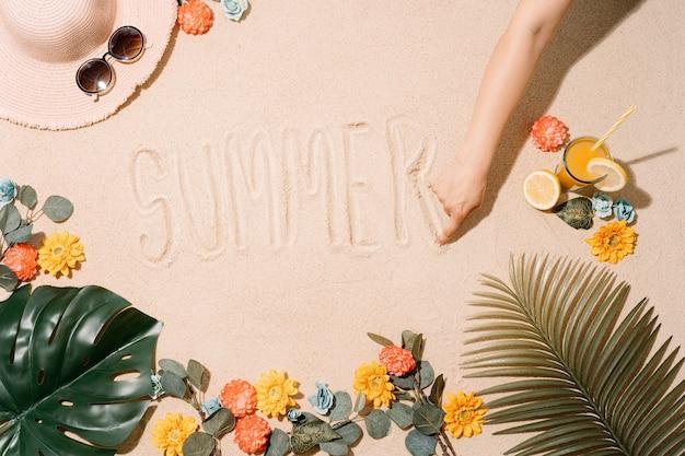 모래 해변에서 그의 손가락으로 여름이라는 단어를 쓰는 알 수없는 사람