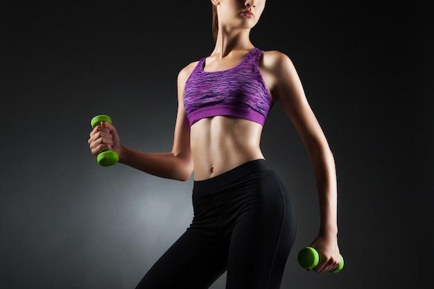 緑のダンベルで上腕二頭筋の運動をしている未知の女性。スタジオポートレート黒ビネット背景。