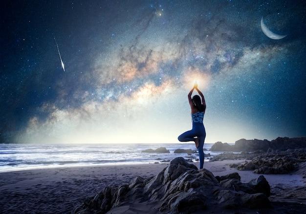 天の川の背景を持つビーチでヨガの木の位置に立っている未知の女性
