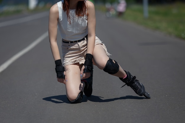 Unknown young girl fell on the road and bruised her knee during skating on warm sunny day Premium Photo