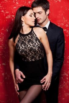 解き放たれた欲望。赤い背景に立っている間結合する美しい若い身なりのよいカップル