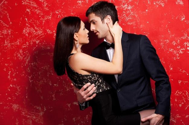 解き放たれた欲望。赤い背景に立っている間抱き合ってお互いを見ている美しい若い身なりのよいカップル