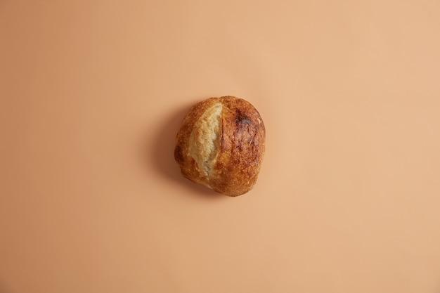 베이지 색 배경에 고립 된 유기농 천연 밀가루에서 준비하는 둥근 모양에 이스트를 넣지 않은 프랑스 빵. 에코 라이프와 유기농 식품 개념. 직접 만든 갓 구운 빵 덩어리. 베이커리 개념