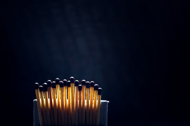 Unlighted matches in a row against a dark background