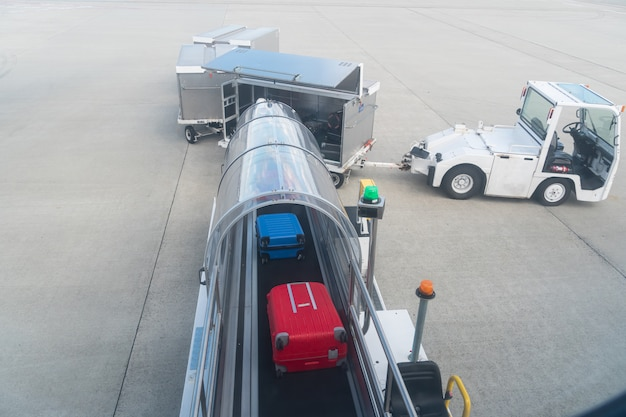Unloading bags and luggage from an airplane.