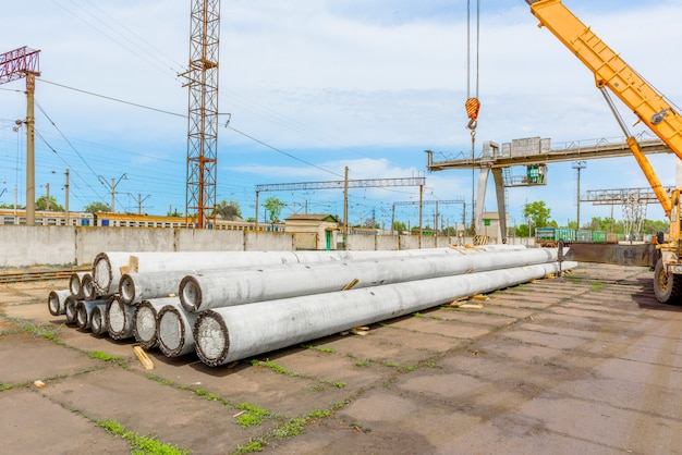 Unloading of concrete high-voltage poles at the construction site using a lifting crane. preparation for high voltage line installation