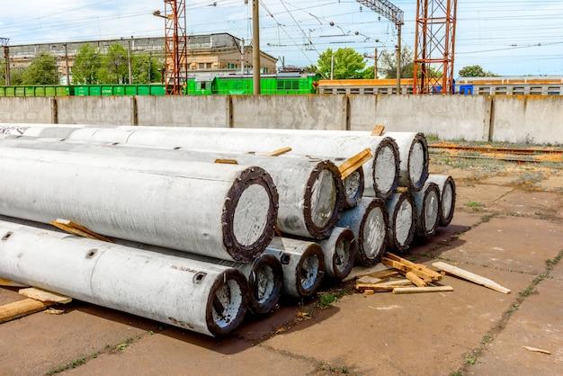 Разгрузка бетонных опор высокого напряжения на строительной площадке с помощью подъемного крана. подготовка к установке высоковольтной линии