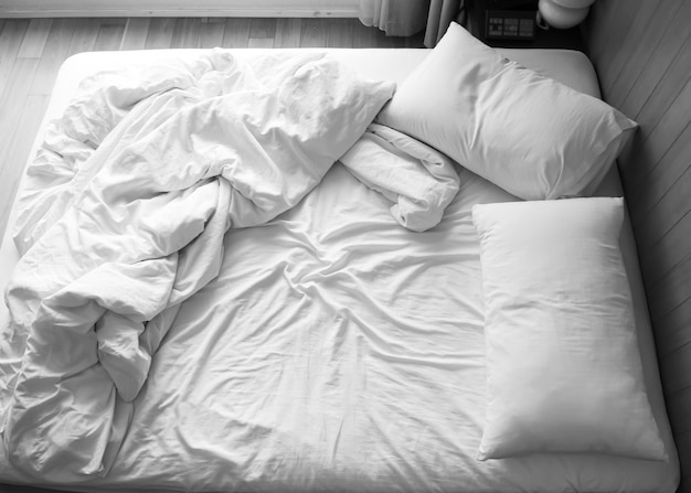 寝室に整えられていないベッド。黒と白の色調