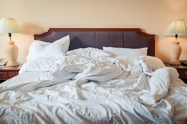 Неубранная кровать с мятой простыней, одеялом и подушками после комфортного пухового одеяла, проснувшись утром