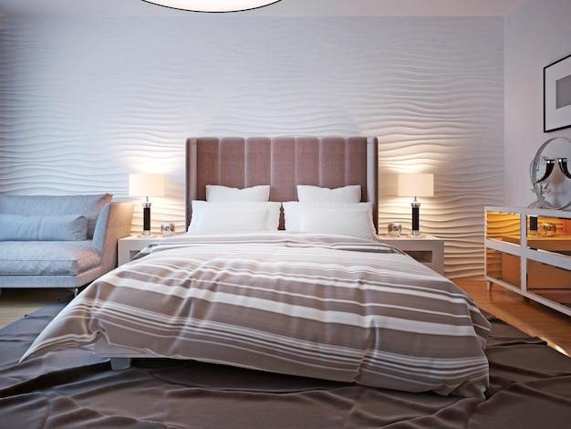 Насыпная кровать с большим изголовьем с двумя прикроватными тумбочками с лампами по обе стороны кровати с большим изголовьем и волнистой стенкой сзади.