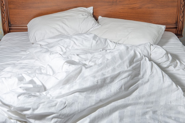 Unmade bed with white linens. unmade empty bed. close up unmade bed sheet