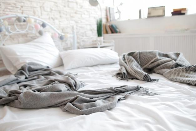 しわの寄ったシーツと毛布を備えた未完成のベッド。