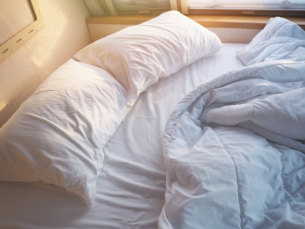 Unmade bedroom in the morning. white pillow and blanket with wrinkle messy on bed.