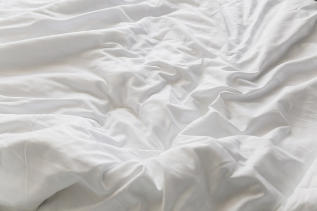 Unmade rumpled bed with white messy pillows  in bedroom interior morning light