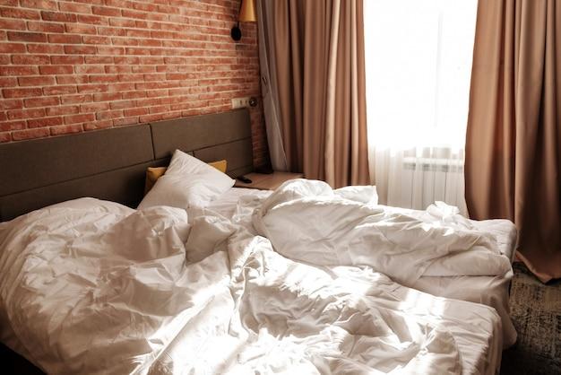 창가에 하얀 담요와 베개가 깔린 침대 2 개를 만들지 않았습니다. 붉은 벽돌 벽으로 로프트 아파트. 미니멀리스트 또는 스칸디나비아 스타일의 인테리어 디자인. 가구가있는 넓은 침실