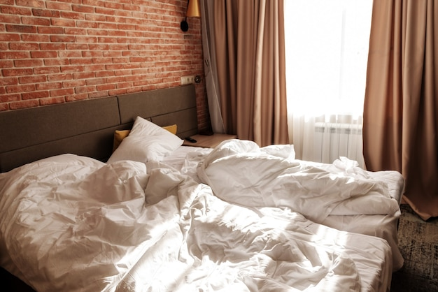 Unmade two beds with white blankets and pillows at window. loft apartment with red brick wall. minimalist or scandinavian style of interior design. spacious bedroom with furniture