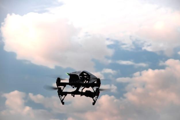 Беспилотный дрон с пропеллерами и цифровой камерой летит в пасмурном небе на фоне розовых облаков и голубого неба