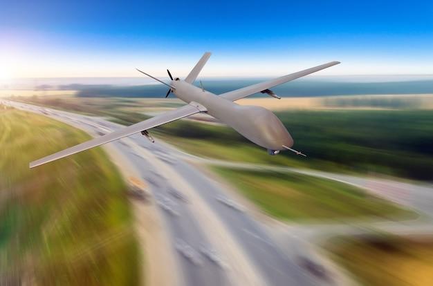 Беспилотный военный самолет на большой скорости летит над шоссе и городом.