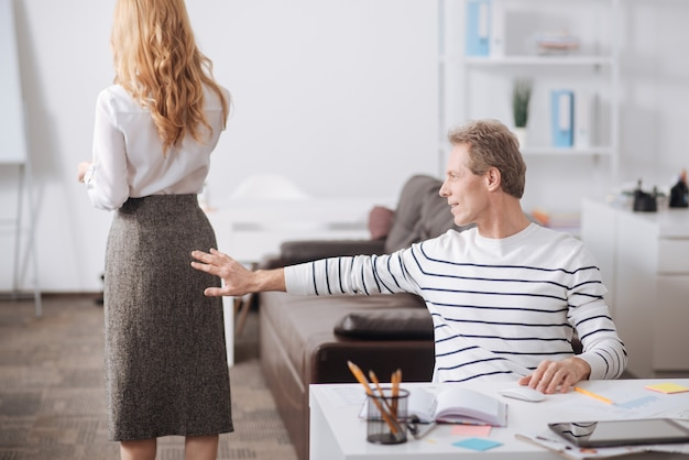 Unmannered smiling mature office manager sitting in the office and working while touching colleagues body