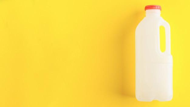 乳製品ゼロの黄色の背景の概念上のマークされていない生分解性プラスチック牛乳瓶は...