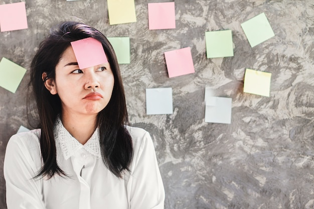 Unmotivated asian woman worker with sticky note