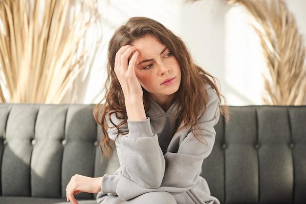 Расстроенная девушка держит голову, у женщины болит голова. грустная женщина сидит на диване
