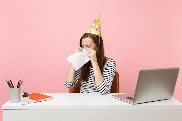 Donna snervata con il cappello da festa che piange asciugandosi le lacrime con un fazzoletto perché festeggia il compleanno da sola in ufficio alla scrivania bianca con il laptop