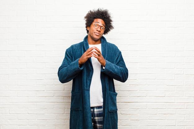 若い黒人男性のパジャマを着て陰謀と陰謀、不正なトリックとチートを考えて、unningなレンガの壁を裏切る