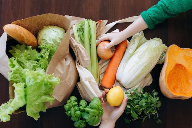 2人の女の子による食料品の買い物の後、新鮮な野菜と野菜のエコバッグを開梱します。健康的な食事の概念。