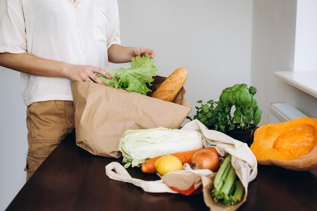 食料品の買い物の後、新鮮な野菜と野菜のエコバッグを開梱します。健康的な食事の概念。
