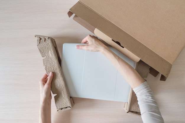 Unpacking a new laptop from a cardboard box. hands open the box. unpacking the received parcel
