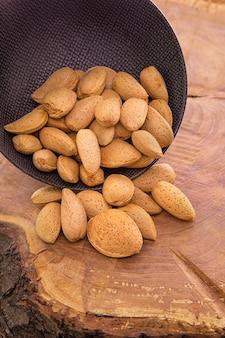 皮をむいていないアーモンドナッツを暗いカップから木製のテーブルに注ぐ