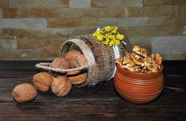 かごの形をした鍋と木製のテーブルの土鍋に入れられた皮をむいて皮をむいたクルミ