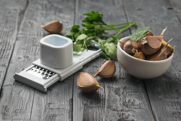 皮をむいていないニンニクと木製のテーブルの上に特別なニンニクおろし金。キッチンに人気のスパイス。