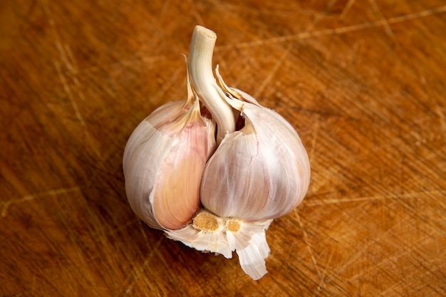 Unpeeled head of garlic isolated on wooden table