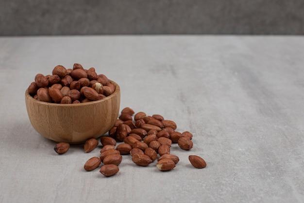 Неочищенные органические арахисы в деревянной миске.