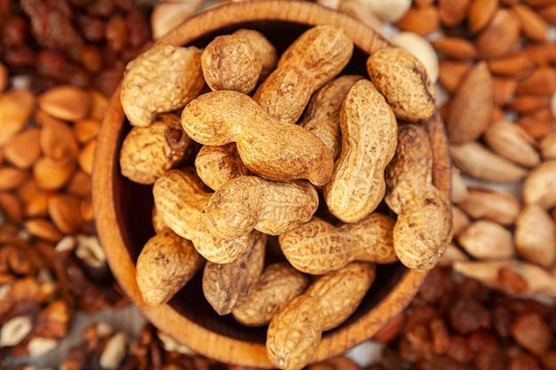 Неочищенный арахис в деревянной кедровой тарелке на фоне россыпи различных орехов.