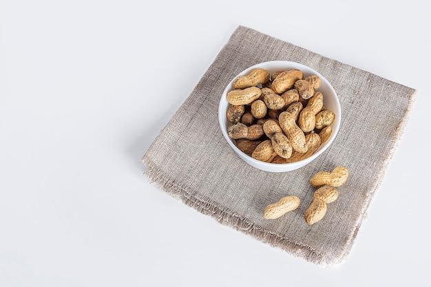 Неочищенный арахис в белой миске на мешковине.